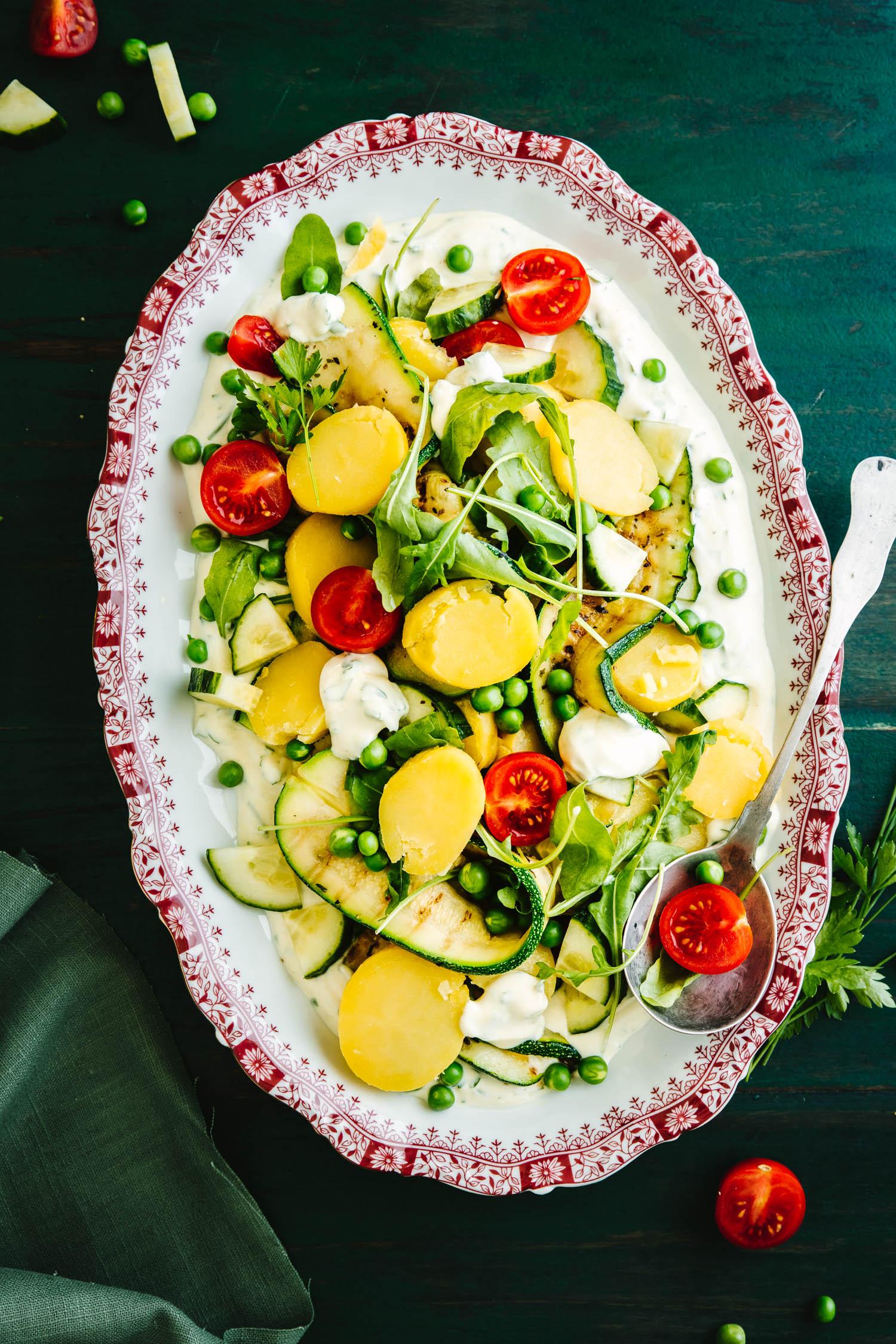Kartoffelsalat mit Quark auf Platte mit rotem Rand und Löffel