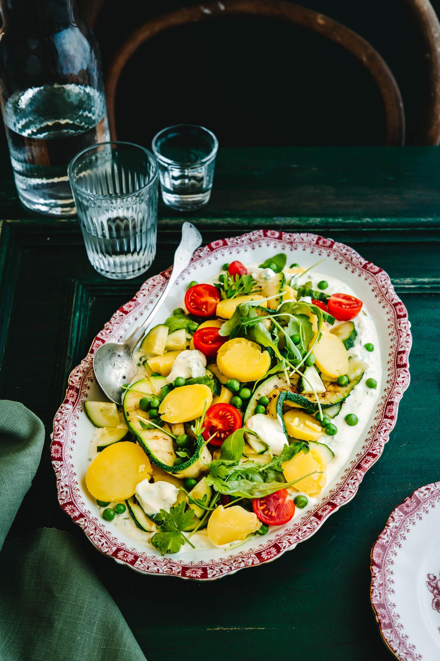 Kartoffelsalat auf grünem Untergrund mit Gläsern daneben